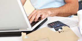 Männerhand bedient Laptop Tastatur, Taschenrechner Briefumschlag, Symbolbild für Clickworker Crowdworker, Crowdworking, Cloudworker, Cloudworking